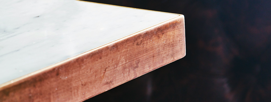 Brushed Metal edge around white marble table top
